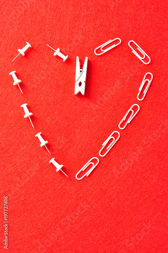 White paperclips, folding clips, push pins and a peg on a
