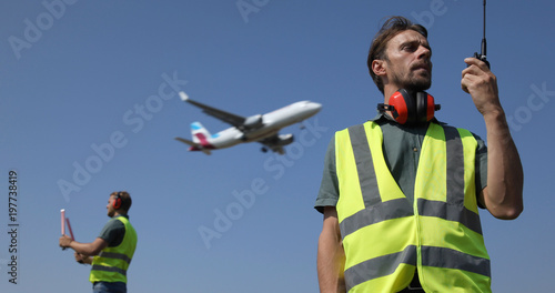 Photo Ground Crew Dialogue with  Air Traffic Control Tower Using a Walkie Talkie, Airp