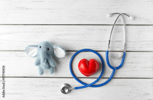 Fotografiet  Cute knitted elephant, small heart and stethoscope on white wooden background