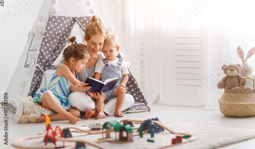 family mother reading to children book in tent at home.
