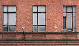 Fragment of the facade of an old brick building. High Windows and textured materials - 197743457