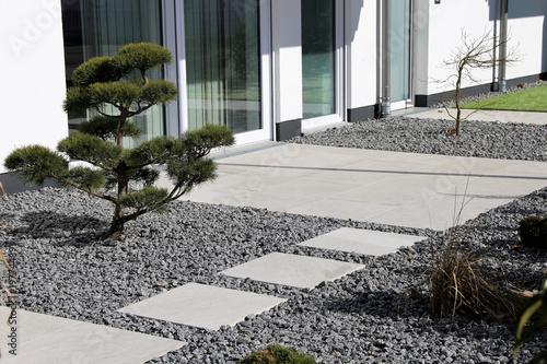 Kleiner Ziergarten mit grauen Terrassenplatten Fototapete
