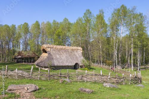 Fotografiet  Bronze age Longhouse in a spring landscape