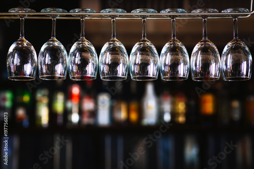 Group of wine glasses hanging above a bar rack in pub & restaurant