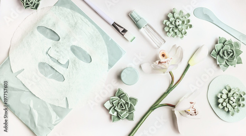 Valokuva  Skin care flat lay with facial sheet mask, mist spray bottle , succulents and orchid flowers on white desktop background, top view