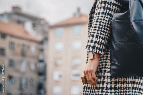 detail shot of a woman outdoors posing in a checked patterned coat, wearing a golden ring and watch and holding a black backpack Canvas-taulu