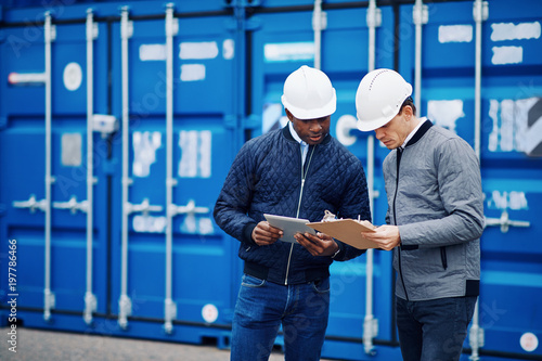 Photo  Two engineers tracking shipping containers in a freight yard