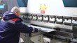 Operator working cut and bending metal sheet by high precision metal sheet bending machine, cnc control metal sheet bending machine in factory