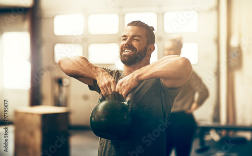 Smiling young man lifting a dumbbell while working out