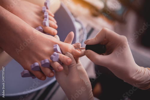 Poster Pedicure Top view close up female manicurist hand in gloves painting nails on feet of lady. Treatment concept