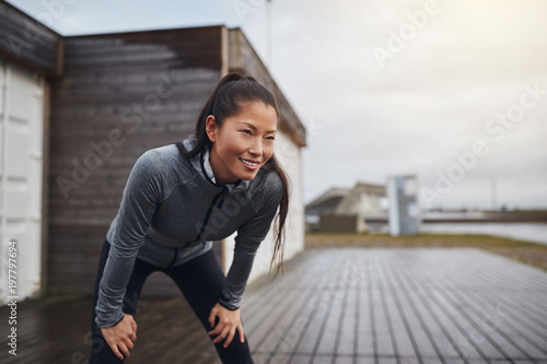 Staande foto Jogging Smiling young Asian woman taking a break while out jogging
