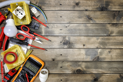 Fototapeta Top view of work tools and electrical system components on rustic wooden background obraz na płótnie
