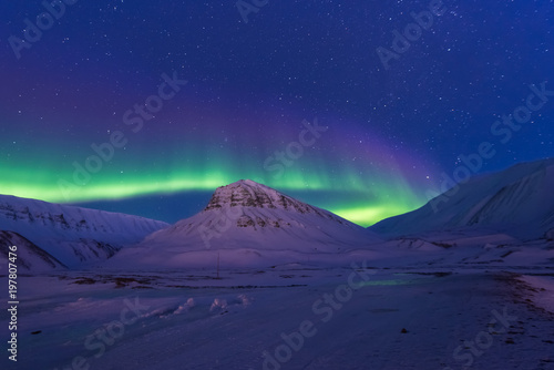Fotobehang Aubergine The polar arctic Northern lights aurora borealis sky star in Norway Svalbard in Longyearbyen city man mountains
