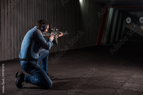 Valokuvatapetti An adult man in jeans clothes, headphones and glasses, holding a Kalashnikov rifle with an optical sight