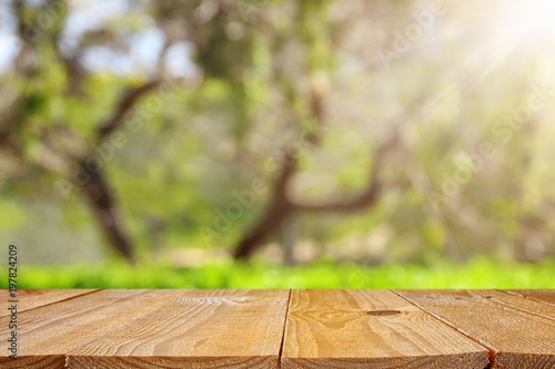 Empty rustic table in front of green spring abstract bokeh background. product display and picnic concept.