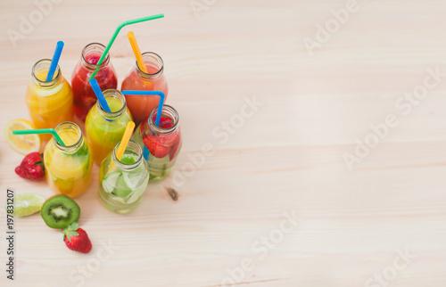 A few glass bottles with different fruit coctails. Billede på lærred