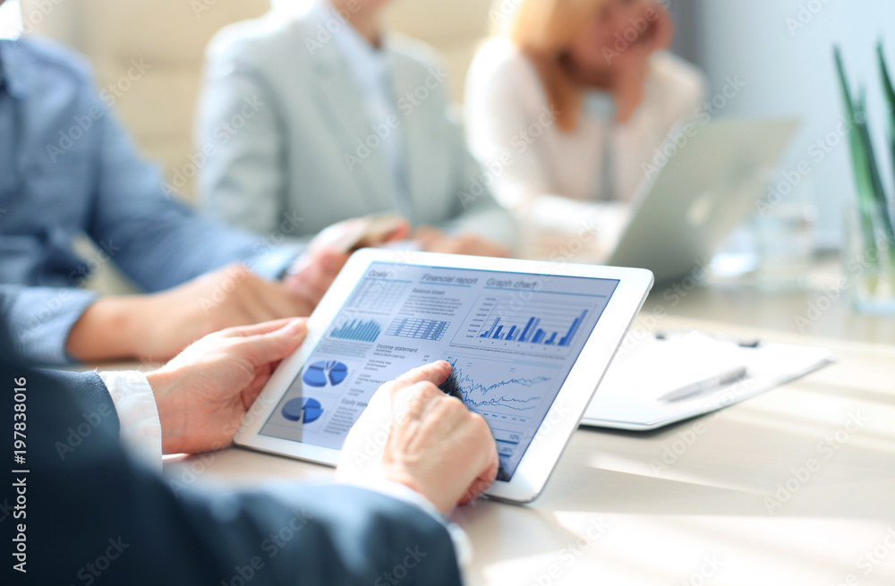Fototapeta Business person analyzing financial statistics displayed on the tablet screen.