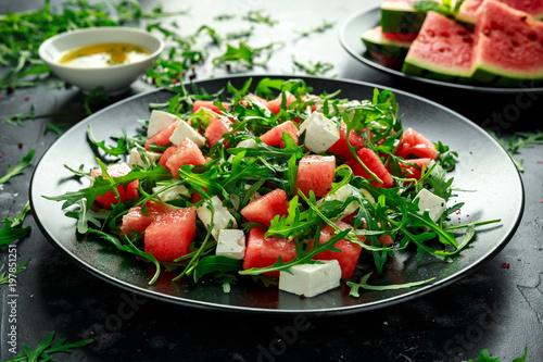 Photo Fresh Juicy Watermelon arugula Feta salad with mint and orange, lemon dressing