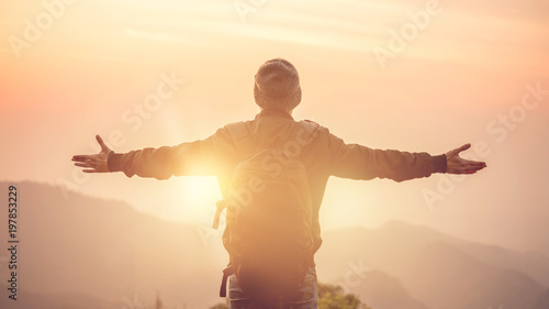 Fotografia Carefree Happy Man Enjoying Nature on top of mountain cliff with morning sunrise outdoor, Freedom concept