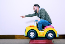 Cheerful Man Riding On Kids Car