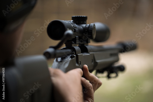 Fotografía  Sniper shooting rifle by looking through a scope.
