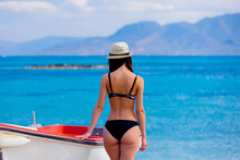 View At Young Girl In Black Bikini Standing Next To Boat Near A Sea In Greece. Summertime Vacation Concept
