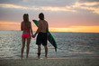Man and a Woman with Surf Boards at Sunset
