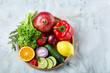 Ripe fresh fruits in a wooden plate on a light background, selective focus, close-up, top view