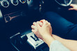 A young couple in love holding hands, holding on the shift lever going into the road trip.