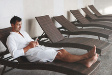 A Young Handsome Man Lies On A Lounger In A Swimming Pool In A White Terry Dressing Gown And Looks At The Smartphone