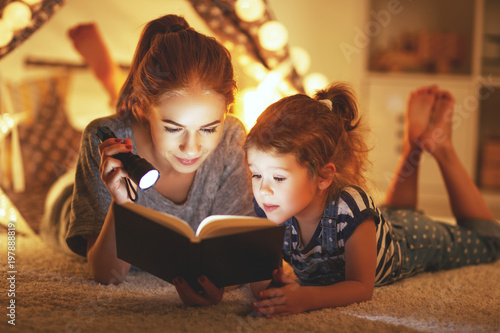 Fotografie, Obraz  mother and child daughter reading a book and a flashlight before going to bed
