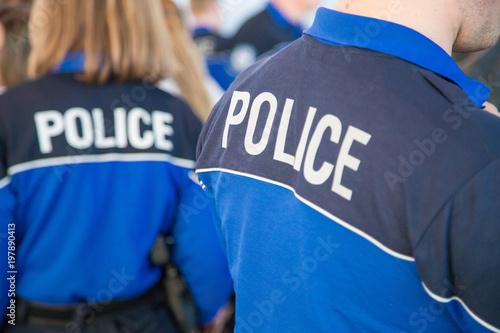 Fotomural  Policier de dos avec sa tenue de service entouré de ses co-équipiers