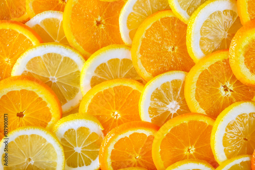 Photo Stands Slices of fruit Abstract background of sliced orange and lemon. Close-up view.