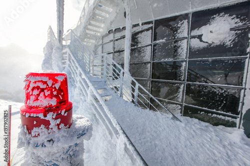 Obraz na plátně  Red emergency lighting with snow and ice covered stairs and windows at top of mountain Chopok ski resort, illustrating extreme cold in the winter