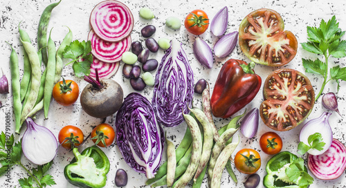 Fresh vegetables background. Cabbage, beets, green beans, tomatoes, peppers on a light background, top view. Flat lay. Vegetarian, diet food concept