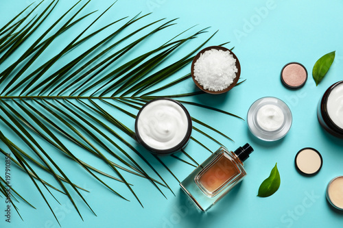 Different skin care cosmetic products with green leaves on color background, top view