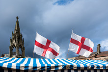 Mansfield In The County Of Nottinghamshire ,English Flags Flying From A Market Stall On The Market Place With Storm Clouds Overhead.
