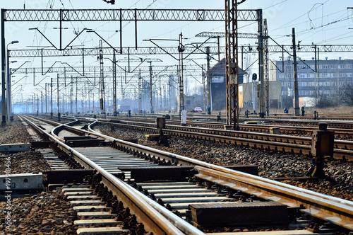 Recess Fitting Railroad Tory kolejowe, słupy i przewody zasilające na tle nieba.