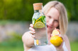 healthy eating, drinks, diet. The girl is holding a detox drink from a lemon and mint with a cucumber on a background of green grass