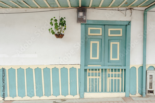 Front door of a colonial house in the small town of Salento with a climbing plant in the left in Salento, Colombia