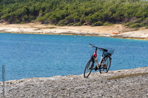 Foto op Plexiglas Bicycle stands on stony beach, Kamenjak peninsula by the Adriatic Sea, Premantura, Croatia, swimming people in background, sunny summer day