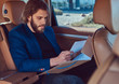 A handsome businessman with a beard and long hair sitting in the back seat of a luxury car and working with documents.