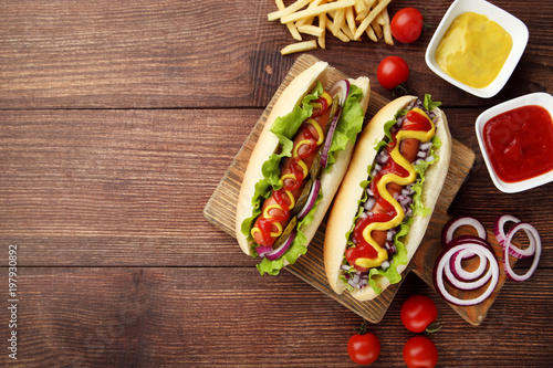 Photo  Hot dogs with vegetables and french fries on wooden table