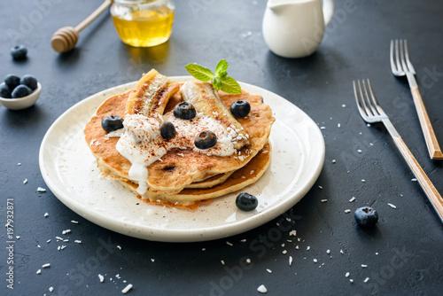 Oat pancakes with greek yogurt, roasted banana, blueberries and cinnamon on white plate