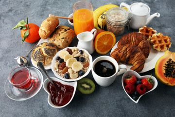 Fototapeta Breakfast served with coffee, orange juice, croissants and fruits. Balanced diet.