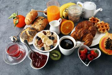 Fototapeta Breakfast served with coffee, orange juice, croissants and fruits. Balanced diet.