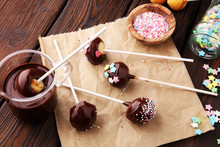 Chocolate Cake Pops On Brown Wooden Vintage Background With Colorful Sprinkles.
