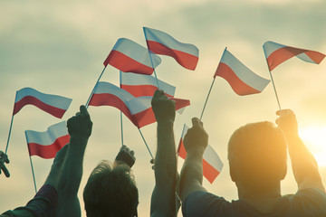 Poland patriots, back view. People raising polish flags up to the sky.