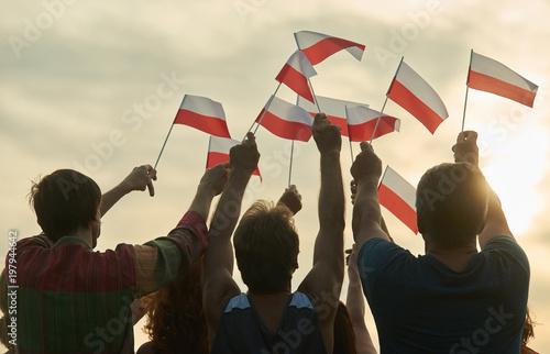 Obraz Waving poland flags. Back view silhouette of polish family. - fototapety do salonu