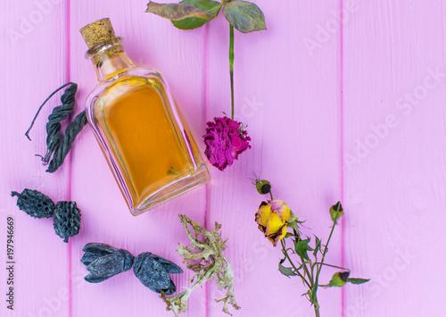 Fototapeta A bottle with a yellow elixir on a pink wooden background. obraz